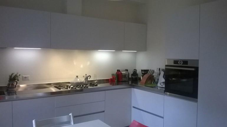 cucina  ad  angolo con  colonne acciaio e bianco