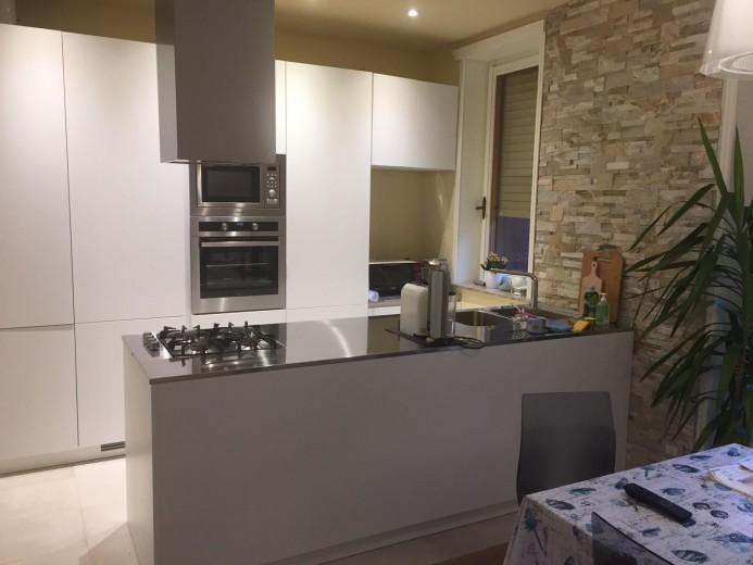cucina con  colonne a  parete e  penisola biaco/inox